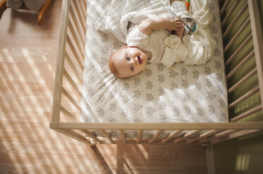 High angle view of cheerful baby boy lying in crib at home - CAVF56818