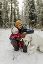 Mother with daughter petting dog in forest during winter - CAVF56845
