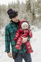 Father carrying cute daughter while standing in forest during winter - CAVF56851