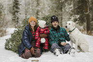 Portrait of parents with daughter and dog sitting by pine tree on snow covered field in forest - CAVF56854