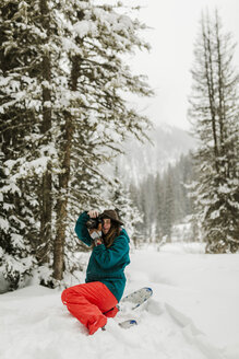 Woman photographing with camera while crouching on snow covered field in forest - CAVF56857