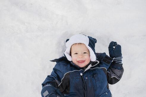 Overhead portrait of cute baby boy lying on snow - CAVF56887