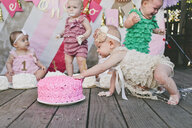 Baby girls with birthday cakes on floorboard at party - CAVF56899