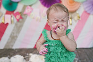 Baby girl crying while eating birthday cake during party - CAVF56905