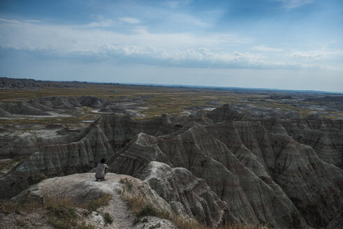 High angle view of hiker crouching on rocks at Badlands National Park against sky - CAVF56953