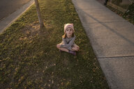 High angle portrait of cute girl sitting by footpath - CAVF56986