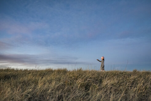 Side view of girl standing on grassy field against sky during sunset - CAVF56992