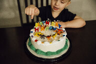 High angle view of boy sitting by birthday cake on chair at home - CAVF57007