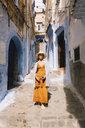 Portrait of woman walking in alley amidst old buildings - CAVF57022