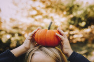 Cropped image of girl balancing pumpkin on head - CAVF57037