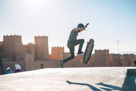 Side view of man performing stunt on skateboard against castle during sunny day - CAVF57058