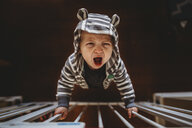 High angle portrait of baby boy crying while standing by railing at home - CAVF57070