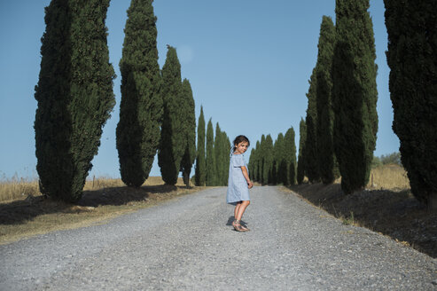 Portrait of girl standing on footpath amidst trees against clear blue sky during sunny day - CAVF57082