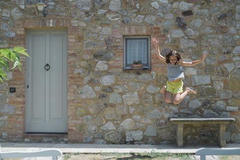 Girl jumping on field at yard - CAVF57085