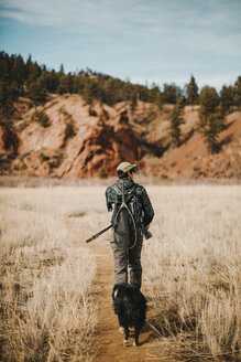 Rear view of male hiker with dog walking on field against sky - CAVF57145