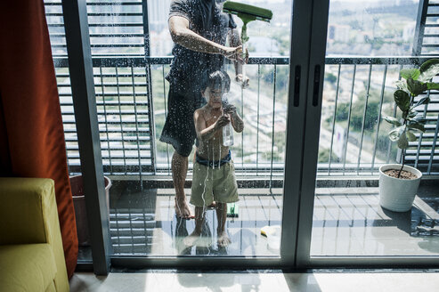 Low section of father with son cleaning windows in balcony seen through glass - CAVF57160