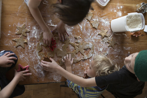 High angle view of siblings preparing cookies on table at home - CAVF57190