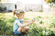 Girl playing with flowers while sitting on grassy field at backyard - CAVF57199