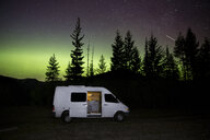 Motor home against aurora borealis at forest during night - CAVF57223