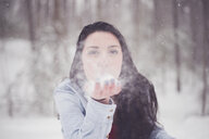 Portrait of teenage girl blowing snow in forest - CAVF57271