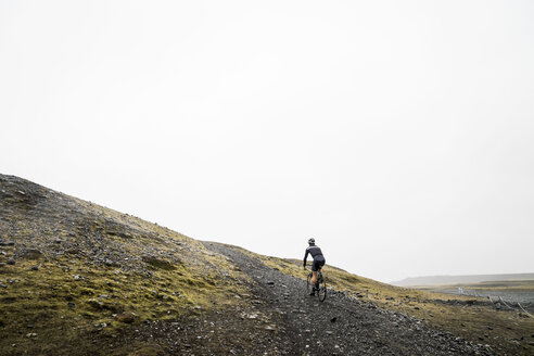 Rear view of male hiker riding bicycle on road against sky - CAVF57283