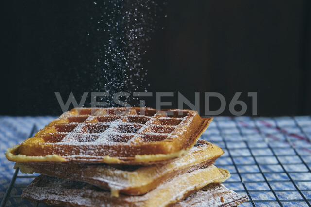Close-up of powdered sugar sprinkling on waffle against black background - CAVF57286