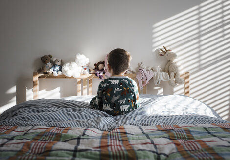 Rear view of boy sitting on bed at home - CAVF57307