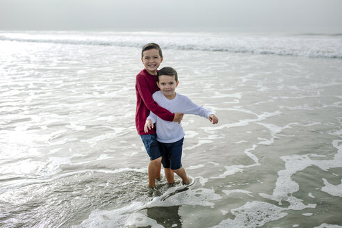 Portrait of cheerful brothers playing in sea - CAVF57322