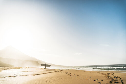 Man with surfboard walking towards sea at beach against sky during foggy weather - CAVF57365