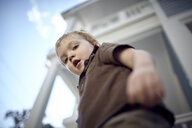Low angle portrait of baby boy standing by building - CAVF57389