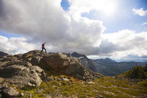 Hiker climbing on rocks against cloudy sky - CAVF57410