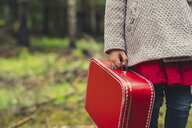 Midsection of girl with red briefcase standing at forest - CAVF57443