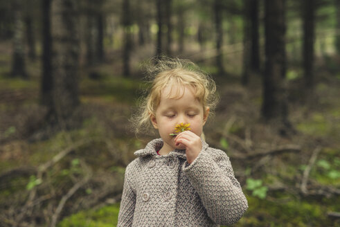 Cute girl with eyes closed smelling flower at forest - CAVF57446