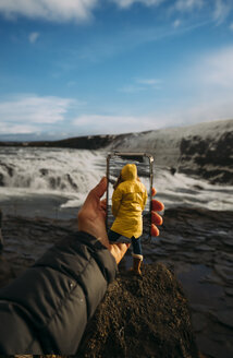 3D montage of man taking smartphone picture of Iceland's landscape and woman wearing yellow raincoat - OCMF00123