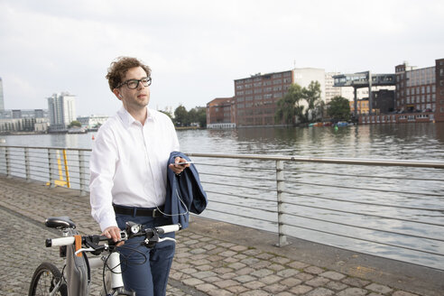 Germany, Berlin, portrait of businessman using smartphone and earphones while pushing his bicycle - FKF03108