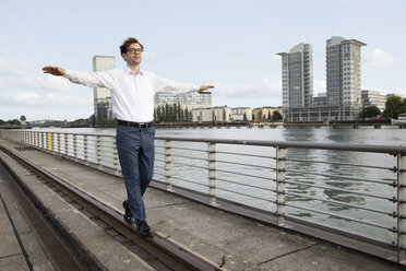 Germany, Berlin, businessman balancing on a rail at River Spree - FKF03114