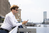 Germany, Berlin, businessman leaning on railing while looking at smartphone - FKF03120