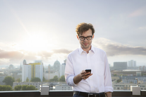 Germany, Berlin, smiling businessman on roof terrace looking at smartphone in the evening - FKF03123