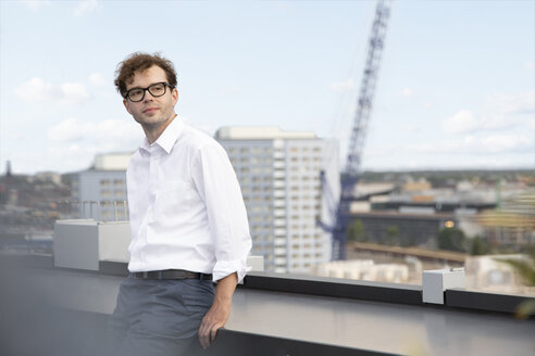 Germany, Berlin, portrait of content businessman standing on roof terrace - FKF03129