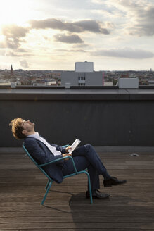 Germany, Berlin, businessman relaxing on roof terrace at sunset - FKF03132