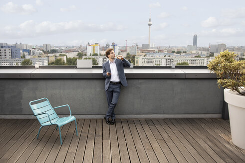Germany, Berlin, businessman having a drink on roof terrace after work - FKF03135