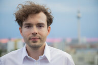 Germany, Berlin, portrait of  businessman with stubble and curly brown hair at sunset - FKF03138