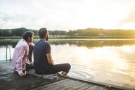 Male friends looking at lake while sitting on jetty during sunset - MASF09701
