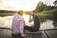 Smiling male friends talking while sitting on jetty over lake during sunset - MASF09704
