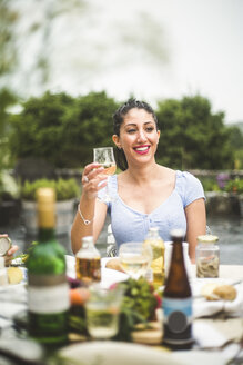 Smiling young woman looking away while enjoying wine at dinner party - MASF09716