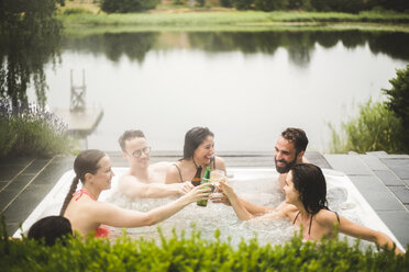 Cheerful male and female friends toasting drinks in hot tub against lake during weekend getaway - MASF09731