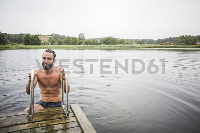 Shirtless mid adult man looking away while climbing ladder on jetty over lake during weekend getaway - MASF09734