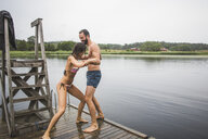 Playful woman pushing male friend in lake while standing on jetty during weekend getaway - MASF09737
