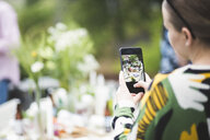 Cropped image of woman photographing dining table through mobile phone in backyard - MASF09743
