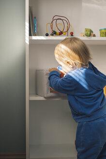 Baby girl taking toys from shelf - MOMF00548